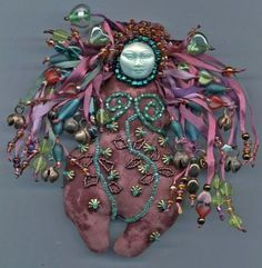 Doll made out of a beautiful mauve batik fabric, stuffed, with a polymer clay face attached.