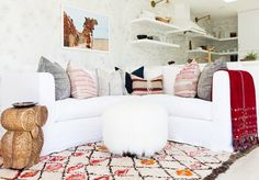 Bright and white living space with patterned rug and red throw