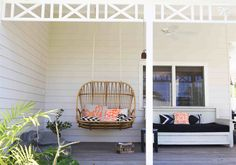 Catch a summer snooze or some reading time in this hanging love seat made from natural rattan.