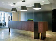 The reception desk combines walnut veneer, brushed bronze, and polished nickel.