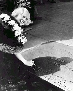 """kitty-packard: Jean Harlow signing her name into the wet cement at Grauman's Chinese Theatre on September 29, 1933. Jean Harlow's second square, which is the one you see today as the first one never made it into the forecourt, contains the inscription """"To Sid In Sincere Appreciation."""" Also included are the date (""""Sept-29-33″), her two tiny footprints made in high heels, handprints, signature as well as three black pennies she embedded in the cement for good luck. The coins have since been…"""