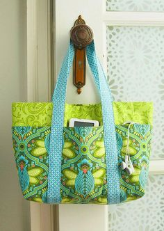 A simple bag cleverly incorporates six outer pockets for everyday  necessities. The sew-simple trick is that the pockets are formed when the  straps are sewn on the bag pieces.