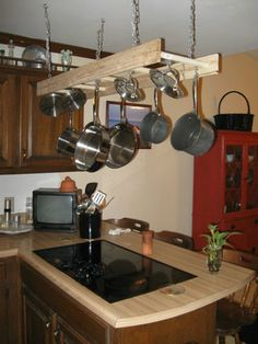 Use an old ladder and hang it or stand it up against the wall to hang pots and pans from.  Please secure it to the wall!!!