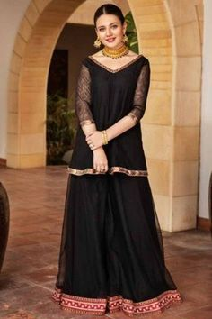 Look elegant when wearing this black net sharara suit which will certainly make you rule to the party. This v neck and 3/4th sleeve wedding wear dress elaborated using lace work. Teamed up with net sharara pants in black color with black net dupatta. Sharara pants has lace. Dupatta is plain. #shararasuits #malaysia #Indianwear #weddingwear #andaazfashion Indian Attire, Indian Wear, Pantalon Cigarette, Sharara Suit, Costume, Wedding Wear, Asian Woman, Elegant, Lace