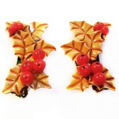 "A pair of festive vintage 1.5"" acrylic holly clip-on earrings in good condition."