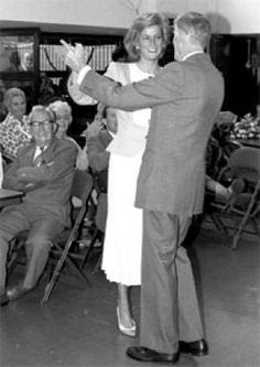 Diana dancing with an elderly gentleman at a retirement center