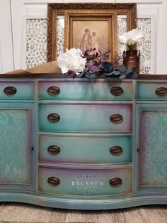 You might remember this one from live this week! This buffet has an irridescent quality, metallics everywhere you look. Done with a base of Dixie Belle Paint Company Boss in white, then mermaid tail and amethyst. A coat of silver metallic tinted to a warm champagne with a bit of chocolate gives it a warm glow. A damask stencil from the NEW [re]design with prima collection done in their diamond dust gilding wax adds interest and sophistication to the doors. The final step was touches of the… Chalk Paint Dresser, Chalk Paint Furniture, Cool Furniture, Gilding Wax, Damask Stencil, Dixie Belle Paint, Paint Companies, Hidden Treasures, Paint Ideas
