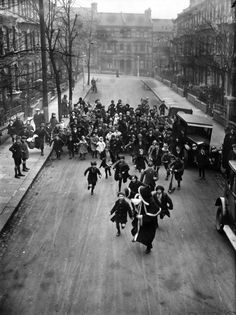 A crowd of happy youngsters chase Father Christmas along a London street. He is on his way to a south London store to distribute presents, 2nd November 1926.