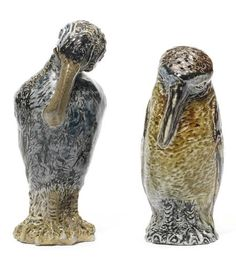 a Pair of Rare Figural Bird Cruets, circa 1880 the taller cruet modelled as a long-billed bird with wings behind it's back, the feathering finely detailed, the companion cruet modelled as a bird with head held close to it's chest, each in tones of cream, blue and brown, having hollow bodies, their heads pierced with vents to facilitate pouring 14cm and 11.5cm high, each signed in a panel to the reverse 'Martin Bros London & Southall' and impressed 'Martin' to base