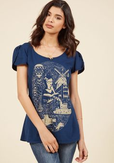 <p>This navy blue top supports your theory that delving into otherworldly delights is as simple as opening up a good book! This cotton tee by LA-based and environmentally-aware brand Blue Platypus touts a wide neckline, tulip short sleeves, and a beige screen print of a lovely gal living it up in the library - just like you!</p>