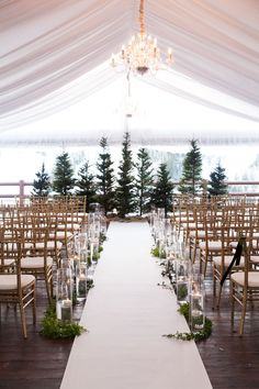 Quem disse que pinheiro só vale no Natal? Tented wedding ceremony with evergreen trees and candles | Winter wedding at Stein Eriksen Lodge in Deer Valley, Utah | Black tie wedding, under a soft fabric tent, with glowing candles, gold Chivari chairs, lush white flowers, evergreens trees and branches, and black accents | Planning: Soiree Productions | Flowers: Decoration Inc. | Photography: Melissa Kelsey Photography | http://www.melissakelseyphotography.com