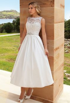 Brides: Demetrios - Destination Romance. Sleeveless, A-line cocktail length dress featuring a taffeta skirt, and Alencon lace bodice with a sheer neckline, and belt with jeweled applique on waist.