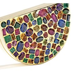18 Karat Gold and Gem-Set Vanity Case, Suzanne Belperron, Paris, Circa 1945. The polished gold case of lunette design, pavé-set in the front with fancy-shaped rubies, sapphires, colored sapphires, emeralds, tourmalines, citrines, amethysts and peridots, the interior fitted with a mirror, removable lipstick case, and small compartment. A similar compact by Belperron was sold in The Jewels of the Duchess of Windsor by Sotheby's in April 1987.