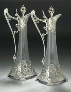 A PAIR OF SILVERED METAL AND CLEAR GLASS CLARET JUGS -  WMF