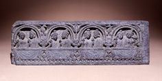 Panel with four inhabited caitya arches above a parapet. Each arch holds a couple of worshippers or spectators: the males wear an uttarīya apparently draped but not looped over the shoulder, a collar, earrings and bracelets, their hair curled and with a chignon; the females wear a sleeved garment and a piece draped over the left shoulder, a necklace, bracelets, earrings, wreath