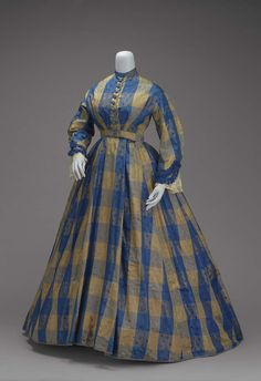 One piece dress of blue and tan large-scale checkerboard plaid; fitted bodice with high, round neck and long sleeves trimmed with blue fringe at bottom; buttoned down front with blue silk-covered buttons; skirt, longer and much fuller in back than front: pocket in right front fold; placket in left front fold; skirt lined with tan glazed cotton; bodice lined in part with tan twill and in part with white cotton. http://www.mfa.org/collections/object/one-piece-dress-of-checkerboard-plaid-89400