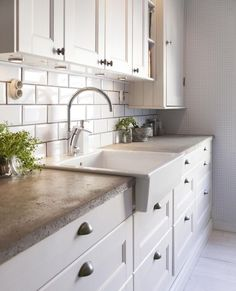 concrete counter, farmhouse sink, white cabinets and nickle hardware