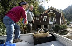 Shireen Malik and Bruce Orr help gather belongings out of the flood-destroyed home of Kathleen McLellan in Salina on Sept. 19, 2013.