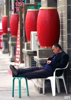 A Chinese man naps next to red drums sitting in front of Communist-themed souvenir shops at a China Revolution tourist site in Yan'an,…