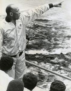 Jesse Owens points towards a track, 1970s
