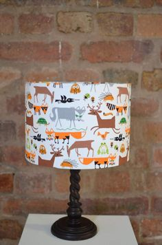A white lampshade made with a fabric featuring woodland animals in brown, grey and orange. This is a beautiful designer fabric that makes the perfect addition to your decor all over the home. This lampshade suits either being used as a table lamp or as a ceiling shade. The lampshade can be made in several different sizes and shapes. If you would like something that is not listed please get in touch. The lampshade is made with a standard UK, Australia and European fitting. US Fittings are…