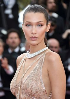 Model Bella Hadid looks bronzed and beautiful with a neutral, contoured makeup look and a tight, high ponytail that shows off her amazingly highlighted cheek bones.