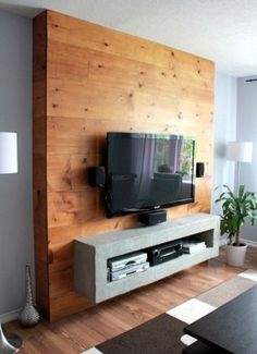 I like the idea of framing the TV with wood planks. I think I might just put some planks directly on the wall and center the TV on it instead of doing floor to ceiling.