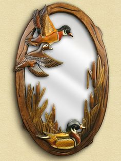 This beautiful hand-crafted mirror features a wood-carved scene of three flying ducks exploring the brush. This mirror is a wonderful functional addition to the wildlife décor in your woodland home, c