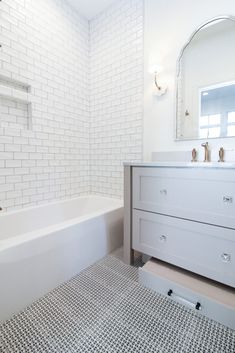 White subway tile shower/tub surround with black and white patterned tile flooring in cute bathroom. White Subway Tile Shower, Bathroom, Relax, Tub Surround, Tile Floor, Black And White, Residential, White Subway Tile, Patterned Floor Tiles