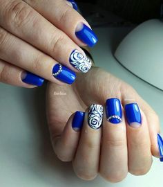 Royal blue and white rose nail art design. The nails are all painted in bright blue nail polish as the background while on the top white nail polish is used to draw and put details on the roses. Embellishments are also added for more effect.