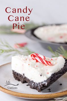 a slice of candy cane pie on a white plate with the pie in the background, candy canes and greens around