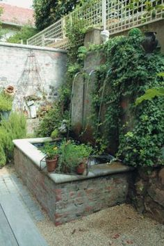 With its simple curved copper pipes, the courtyard water feature is typical of those found all over Europe. It was designed to complement the rough brick walls which give the house its distinctive French Farmhouse look.