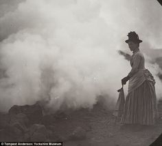 Victorian explorers: A woman wearing a long dress and clutching a parasol poses in front of billowing clouds of smoke, in one image from Tempest Anderson's collection, which has recently been digitised