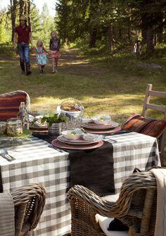 Comedor en un jardín. Sillas de fibra y mantel a cuadros