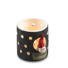 """Fyrfadslygte i Santa High Hat serien. Str. ca. højde: 7,5 cm - diameter: 6,5 cm. En rigtig hyggespreder fyrfadsstage med en lille nisse i åbningen ind til lyset. Masser af små huller, som lyset kan komme ud igennem. Teksten """"GOD JUL"""" skrevet under nissen.Designet af Ruth Vetter. Leveres uden"""