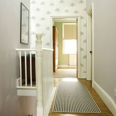 Simple colours and pretty wallpaper add natural brightness to this fresh white hallway.
