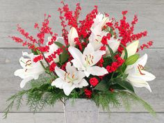 """The perfume of Oriental lilies mingles with the scent of fresh-cut cedar to make this floral arrangement, called """"Deck the Halls"""", smell """"magical, like Christmas,"""" Prescott says. The Oriental lilies are 'White Cup' and the greenery is 'Port Orford', a cedar from the forests that surround Stargazer Barn."""
