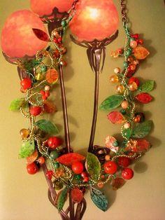Una nuova collana montata con fili di rame colorato intrecciati, su cui sono fissate foglie in polyshrink, conterie, mezzi cristalli, agate...
