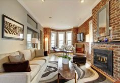 This Denver home's exposed brick walls, fireplaces and high ceilings are to die for.