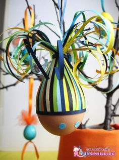 Cut quilling paper into strips of equal length and glue them in the middle of the egg so as to form a circle. Cover jagged edges of eggshell with a strip. Now gather all the tips and tie them into a bundle . Leave two uncurled for a hanging loop, and curl all the rest with scissors.