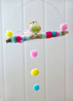 Yarn wrapped branch with bird and pom poms