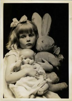 Vintage photo of little girl with doll and stuffed rabbit.