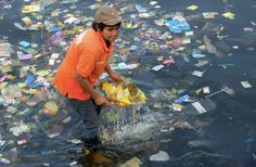 A volunteer collects rubbish in Manila Bay in the Philippines.