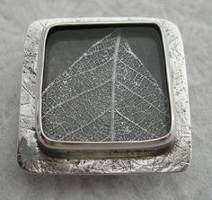 Carla Pennie McBride - Hand-fabricated sterling silver brooch encasing pressed silver leaf on oxidised silver behind plexi-glass. Silver surround also textured using natural leaves in rolling press. Oxidised and polished.