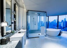 In this modern hotel bathroom, a white standalone tub sits in front of the glass enclosed large shower, and faces the city of Beijing. The bathroom decor is minimal, allowing the city view to be the main decorative element.