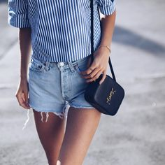 Street style, casual outfit, spring chic, summer chic, striped blouse, ripped shorts, small black shoulder YSL bag