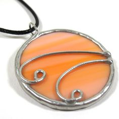 A light orange streaked stained glass pendant edged in silver, with silver wire swirl accents. A 16-18 adjustable soft black cord with lobster clasp included.    Actual Size: 2 x 1 5/8    Each item by Faerie Glass is 100% uniquely hand-crafted with quality materials that are lead-free.    NOTE - All photographs are taken in effort to best represent the actual product. Color of actual jewelry may vary slightly from photographs.