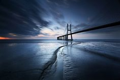"""stopping the #bridge by carlos resende #blue #beauty #photography #DigitalInConstruction #Edifice #LongExposure #Canon EOS 5D MKII + Canon EF 17-40 f/4 L USM @ 17 mm  Long Exposure - ISO 200 - f/13- 303s + Lee Big Stopper + Lee GND 0.9 HE + Heliopan CPL 105mm This is a """"mythical"""" spot in Lisbon that was been photographed from different angles, seasons and times of the day."""