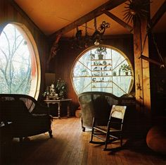 .:  round windows + wood walls & floors  :. (I love the shelves in the window, and the things hanging from the beam.)
