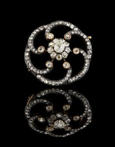 A Fabergé gold and diamond brooch, August Hollming, St. Petersburg, 1898-1908. Circular, with swirling spirals encrusted with rose-cut diamonds, centered with a larger diamond rosette.